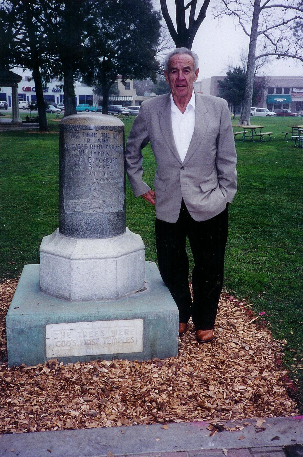 Judge James R. Ross beside the historical monument that commemorates his cousin, Drury Woodson James, founder of Paso Robles California. The memorial stands in the park D.W. James donated to the city.